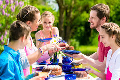 Family having coffee and cake in garden at house Royalty Free Stock Image