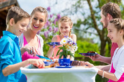 Family having coffee and cake in garden Stock Images