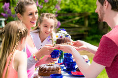 Family having coffee time in garden eating cake. Happy Family having coffee time in garden eating cake royalty free stock photo