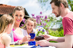 Family having coffee time in garden eating cake Royalty Free Stock Photos