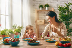 Family having dinner. Happy family having dinner together sitting at the rustic wooden table. Mother and her daughter enjoying family dinner together Royalty Free Stock Photo