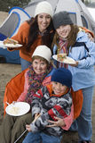 Family Having Food In Front Of Tent Stock Image