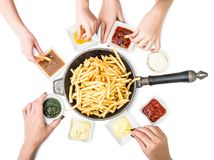 Family having french fries for dinner top view. Family having french fries with different sauces for dinner on a white background. Top view stock photo
