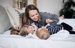 Free Family Having Fun At Home. Happy Young Mother Playing With Children In Bedroom. Brother And Sister Embracing On The Bed. Sunny Hol Royalty Free Stock Photos - 132535298