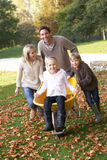Family having fun with autumn leaves in garden
