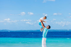 Family Having Fun on Beach. Father with her son having fun on beautiful sunny beach Royalty Free Stock Images