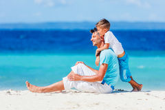 Family Having Fun on Beach. Father with her son walking on beautiful sunny beach Stock Photos