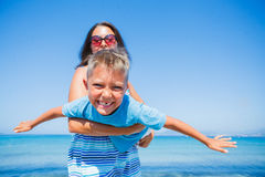 Family Having Fun on Beach. Mother with her son having fun on beautiful sunny beach Stock Image