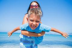 Family Having Fun on Beach. Mother with her son having fun on beautiful sunny beach Royalty Free Stock Photography