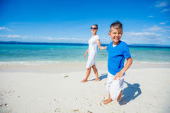 Family Having Fun on Beach. Mother with her son walking on beautiful sunny beach Stock Image
