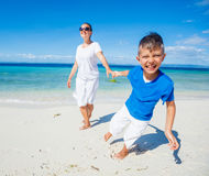 Family Having Fun on Beach. Mother with her son walking on beautiful sunny beach Royalty Free Stock Image