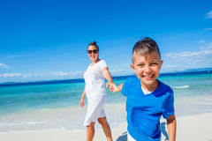 Family Having Fun on Beach. Mother with her son walking on beautiful sunny beach Stock Photo