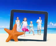 Family having fun on the beach with tablet pc frame Royalty Free Stock Images