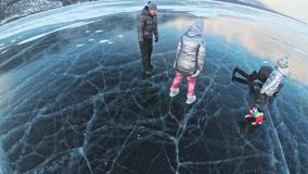 Family is having fun on beautiful ice in cracks. Father mother son and daughter funny fight on ice, make sandwich and. Rest. Man, woman and children are resting stock video