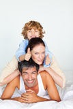 Family having fun in bed with thumbs up Royalty Free Stock Images