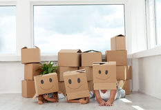 Family having fun with cardboard boxes. Moving into their new home Royalty Free Stock Photography