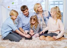 Family having fun on carpet and playing with cute bunny. Royalty Free Stock Photos