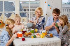 Family having fun and enjoying flavored tea with cupcakes. Royalty Free Stock Photo