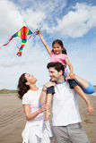 Family Having Fun Flying Kite On Beach Holiday. Flying A Kite Royalty Free Stock Images
