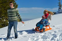 Family having fun on fresh snow at winter vacation Stock Photo
