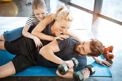 Family having fun at gym, man holding dumbbells Royalty Free Stock Images