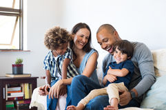 Family having fun at home. Happy multiethnic family sitting on sofa laughing together. Cheerful parents playing with their sons at home. Black father tickles his Stock Images