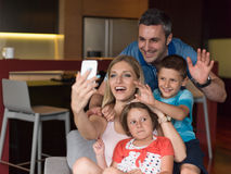 Family having fun at home. Happy family siting on sofa and using cell phone for video call at home royalty free stock photos