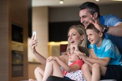 Family having fun at home. Happy family siting on sofa and using cell phone for video call at home royalty free stock photo