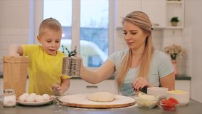 Family having fun on the kitchen. Front view of Cute little boy and his beautiful mom in colorful bright shirts are stock footage
