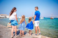 Family having fun outdoors on Mykonos streets. Family vacation in Europe. Parents and kids at street of typical greek traditional village with white walls and Stock Images