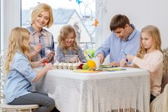 Family having fun painting and decorating easter eggs. Royalty Free Stock Image