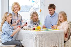 Family having fun painting and decorating easter eggs. Royalty Free Stock Photo
