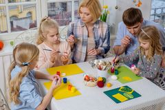 Family having fun painting and decorating easter eggs. Royalty Free Stock Photography