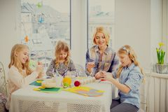 Family having fun painting and decorating easter eggs. Cheerful mother and her daughters painting and decorating easter eggs Royalty Free Stock Images