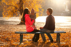Family having fun at park on bench near river Stock Photo