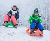 Family having fun with sled in winter park Royalty Free Stock Images