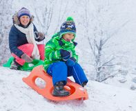 Family having fun with sled in winter park Royalty Free Stock Photos