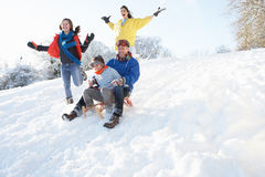 Family Having Fun Sledging Down Snowy Hill Stock Photo