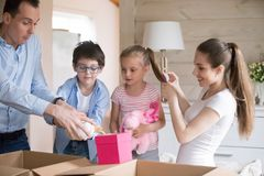 Family having fun unpacking on moving day to new house royalty free stock photos