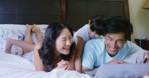 Family having fun while using laptop in bedroom 4k. Family having fun while using laptop in bedroom at home 4k stock footage