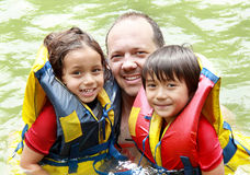 Family having fun the water. Cheerful family in the water wearing life vest smiling at camera royalty free stock photo