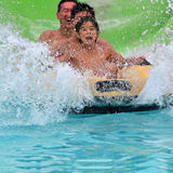 Family having fun at a water park. Asian Family having fun tubing going through a waterfall in  waterpark Stock Photography