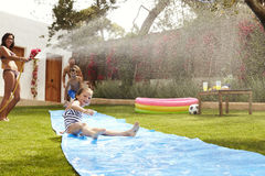 Family Having Fun On Water Slide In Garden Stock Images