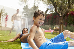 Family Having Fun On Water Slide In Garden Stock Photography