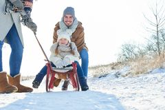 Family having fun in winter. Family with child on sled having fun in winter royalty free stock photos