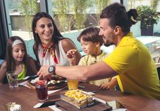 Family having great time in a restaurant. A four-member family having great time in a restaurant stock images