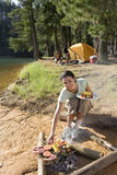Family having lunch on camping trip by lake, focus on woman cooking food in foreground, smiling, portrait Stock Photo