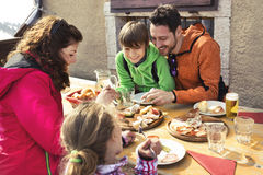 Family having lunch in a chalet in mountain Royalty Free Stock Images