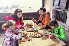 Family having lunch in a chalet in mountain Stock Images
