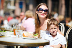 Family having lunch outdoors. Young mother and her son having lunch in outdoor restaurant on summer day Royalty Free Stock Image